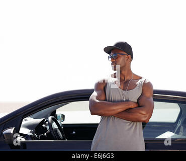Image of young african man standing by his car. Muscular male model wearing sunglasses and cap outdoors. - Stock Photo