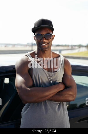 Portrait of handsome African guy with his arms crossed leaning against a car smiling. Stylized muscular guy wearing - Stock Photo