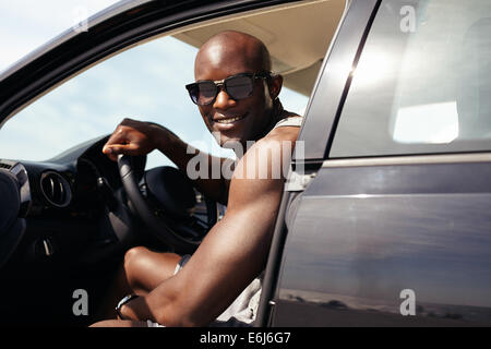 Portrait of happy young guy in his car looking at camera smiling. African male model wearing sunglasses. Muscular - Stock Photo