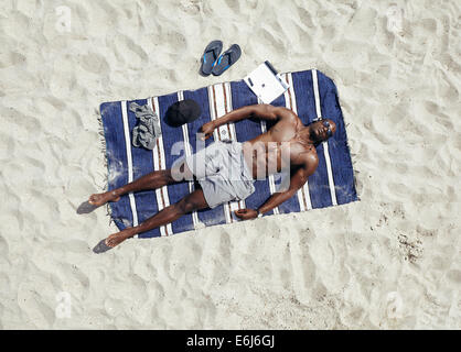 Top view of young guy lying shirtless on a mat sunbathing. African male model relaxing on beach on a hot summer - Stock Photo