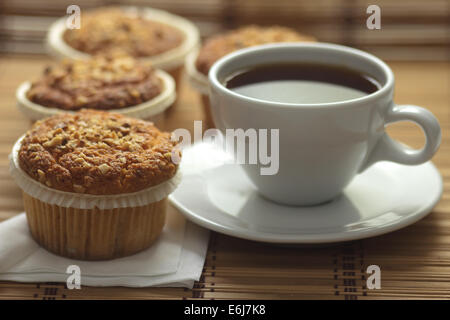 Muffins topped with ground hazelnuts served with tea. - Stock Photo