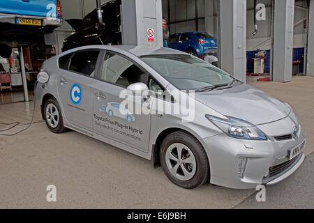 Toyota Prius Plug In OLEV ultra low emission mid-size plug-in hybrid electric vehicle parked - Stock Photo