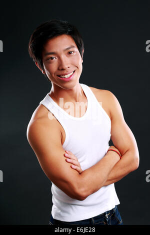 Portrait of a smiling asian man with arms folded on black background - Stock Photo