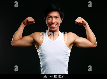 Smiling asian muscular man with arms stretched out on black background - Stock Photo