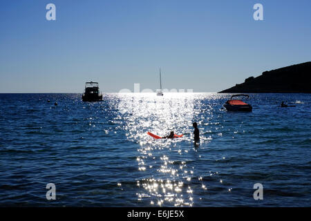 View from Croatian beach across sparkling Adriatic sea with silhouetted swimmers with lilo - Stock Photo