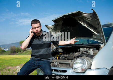 Sad man calling the tow truck for car service - Stock Photo