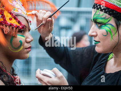 London, UK. 25th Aug, 2014. a woman puts make up on a reveller during the Notting Hill Carnival in London. Credit: - Stock Photo