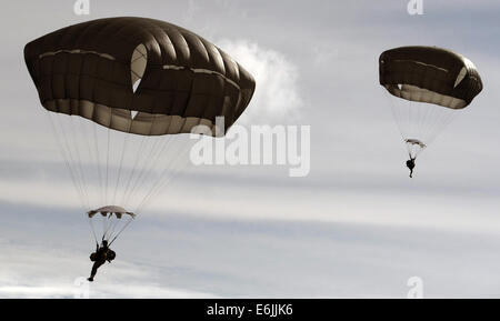 US Army paratroopers with the Airborne 4th Infantry Brigade Combat Team descend into a lake during a water jump - Stock Photo