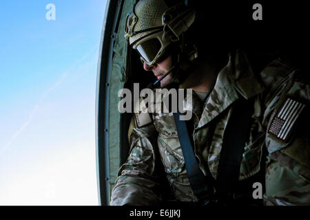 US Air Force Tech. Sgt. Justin McCaffrey watches for possible simulated enemy threats from the open door of a helicopter - Stock Photo