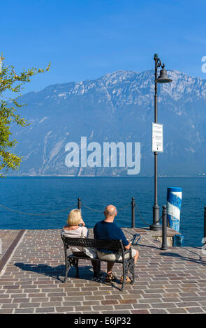 Middle aged couple sitting on the lakefront in Limone sul Garda, Lake Garda, Lombardy, Italy - Stock Photo