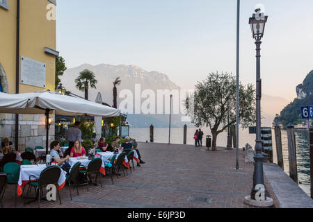 Restaurant on the harbourfront at sunset in the old town, Riva del Garda, Lake Garda, Trento, Italy - Stock Photo