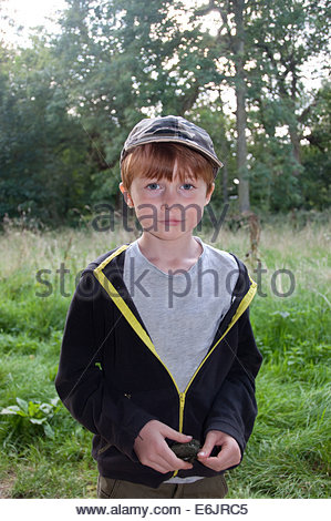 An eight year old, red headed boy, photographed at some woods in Norfolk. - Stock Photo