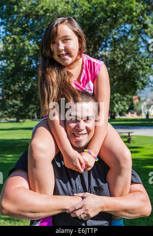 Father holding his seven year old daughter on his shoulders - Stock Photo