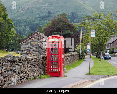 A red telephone box and bus stop in a British rural village - Stock Photo