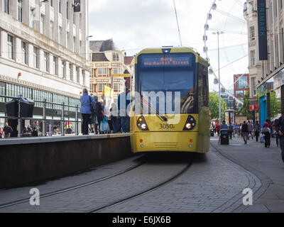 A Tram and shoppers on Market Street in Manchester city centre, England - Stock Photo