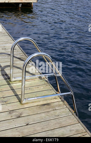 handrails and ladder on wooden jetty - Stock Photo
