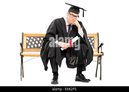 Angry college graduate holding a diploma isolated on white background - Stock Photo