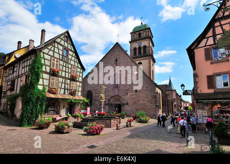 Half-timbered house and fountain in front of the Church of Sainte-Croix on the Rue du Général de Gaulle, Kaysersberg, - Stock Photo
