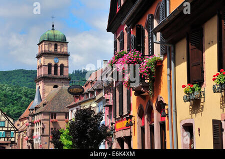 Houses on Rue du Général de Gaulle in front of the Church of Sainte-Croix, Kaysersberg, Alsace, Haut-Rhin, France - Stock Photo