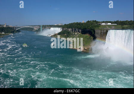 View of American and Canadian (Horseshoe) Falls in Niagara Falls. 'Maid of the Mist' boats carry tourists towards - Stock Photo