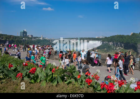 Tourists visiting Niagara Falls, Ontario, Canada. American Falls and Rainbow Bridge in distance. - Stock Photo