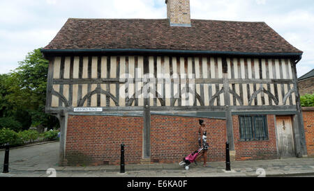 A woman walking on Orford Road past 'The Ancient House' with shopping trolley Walthamstow North East London E17 - Stock Photo