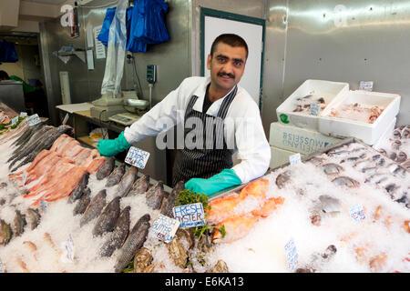 Fishmonger and fish display on ice in N & A fish shop Walthamstow High Street London UK   KATHY DEWITT - Stock Photo