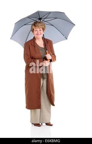 happy retired senior woman holding an umbrella on white background - Stock Photo