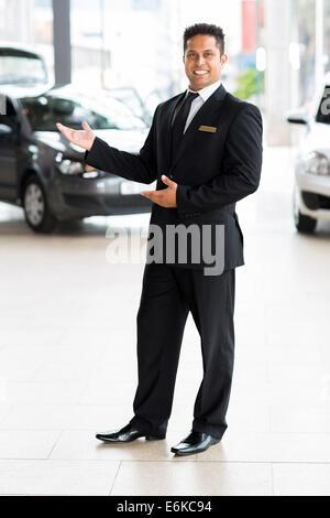 cheerful Indian car salesman doing welcoming gesture - Stock Photo