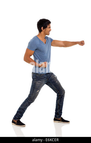 side view of Indian man doing karate in casual clothes - Stock Photo