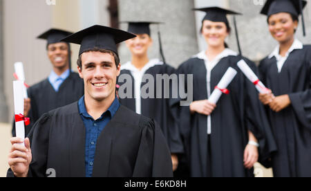 handsome male university graduate holding his diploma - Stock Photo