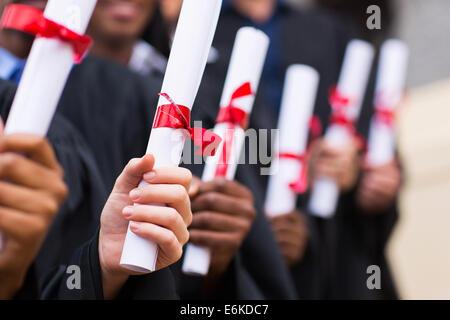 group of multiracial graduates holding diploma - Stock Photo