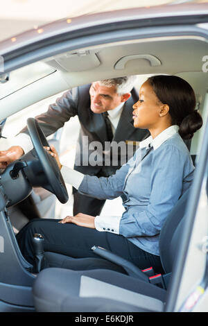 happy senior salesman showing a new car to an African woman - Stock Photo