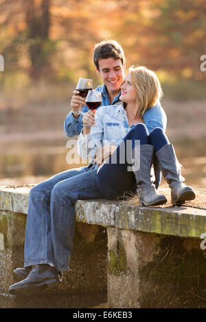 romantic couple drinking red wine outdoors - Stock Photo