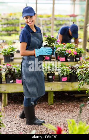 portrait of young florist holding a pot of flowers in greenhouse - Stock Photo