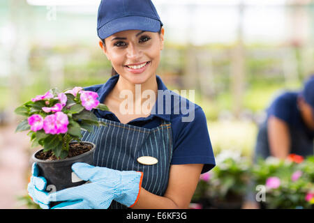 young female gardener holding flowers in greenhouse - Stock Photo