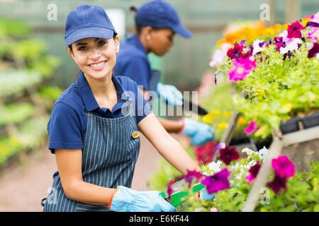 pretty female florist working in nursery - Stock Photo