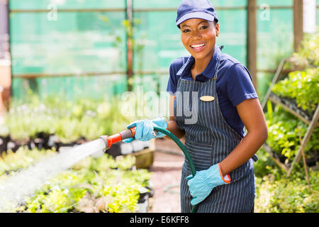 happy African female nursery worker watering plant - Stock Photo