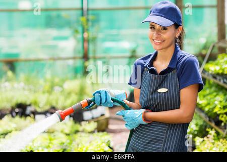 happy florist watering flowers in greenhouse - Stock Photo