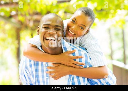 happy African woman enjoying piggyback ride on boyfriend outdoors - Stock Photo