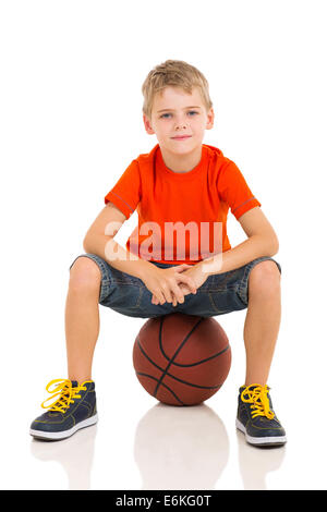 cute kid sitting on a basketball isolated on white - Stock Photo