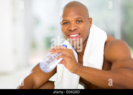 black man drinking water after exercise in gym - Stock Photo