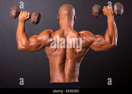 rear view of African bodybuilder training with dumbbells - Stock Photo