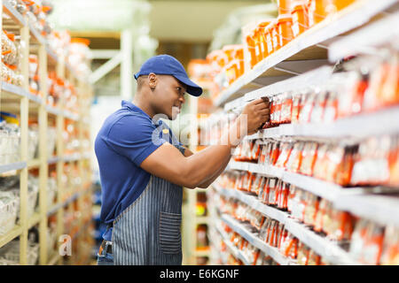 happy African American hardware store worker working in the shop - Stock Photo