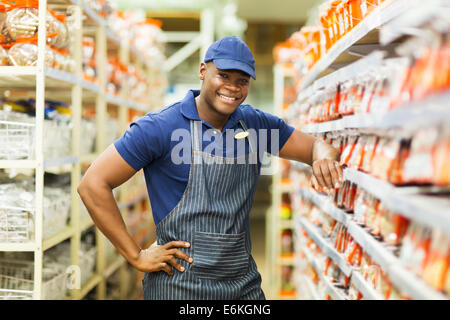 smiling African hardware store worker standing by the fasteners aisle - Stock Photo