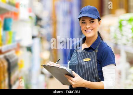 happy female clerk working in supermarket - Stock Photo