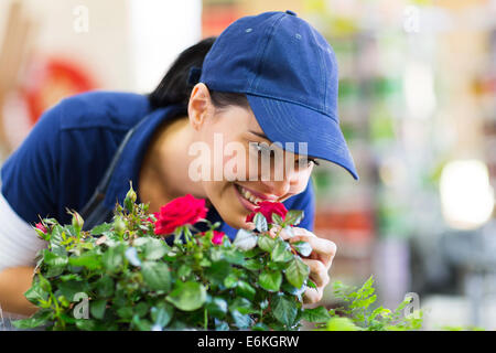 happy female florist smelling flower in nursery - Stock Photo