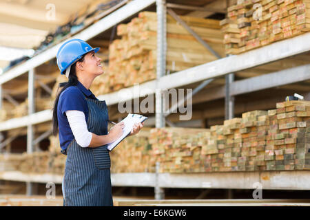 gorgeous female worker stock taking in warehouse - Stock Photo