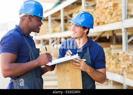 two male hardware store workers working in timber yard - Stock Photo