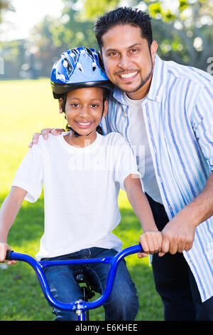 young Indian girl on a bike with her father standing next to her - Stock Photo